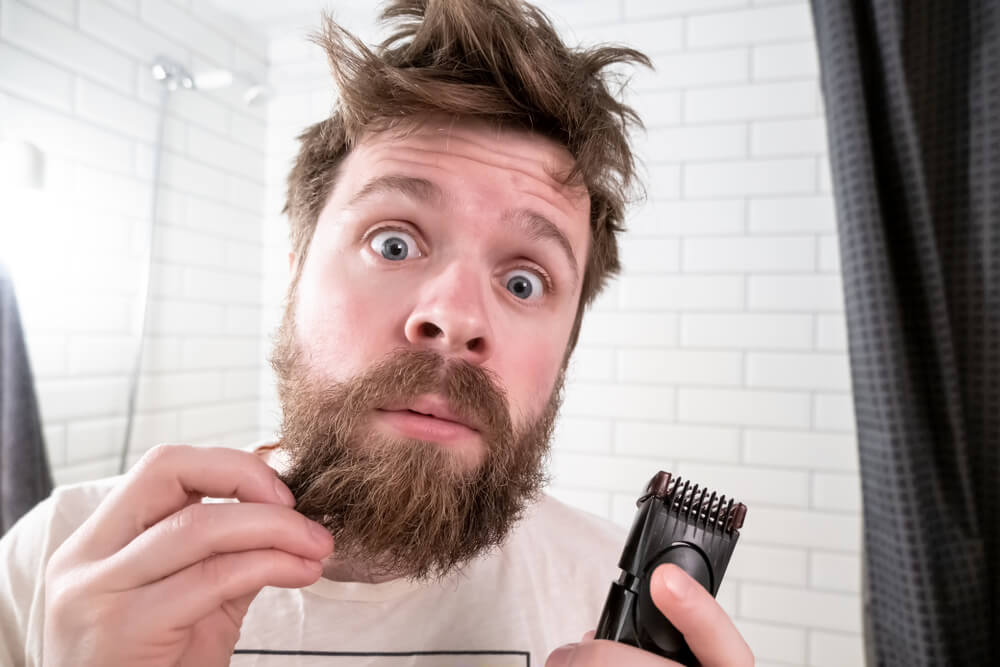 long bearded man with trimmer