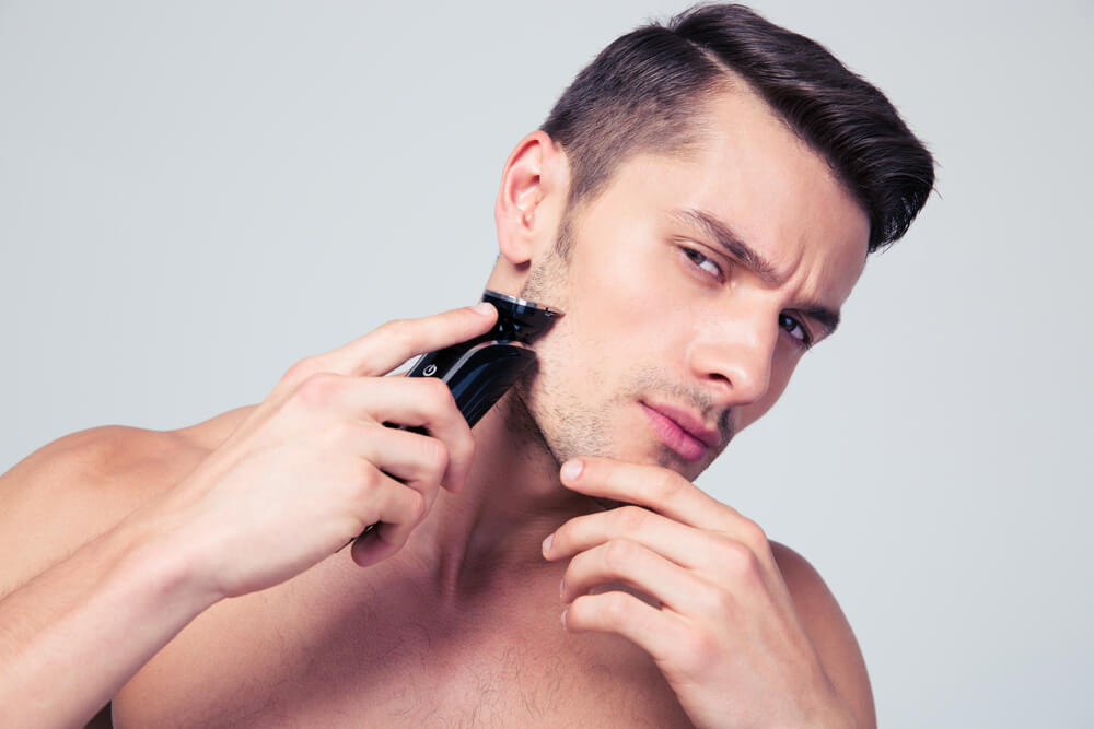 young man trimming with black trimmer