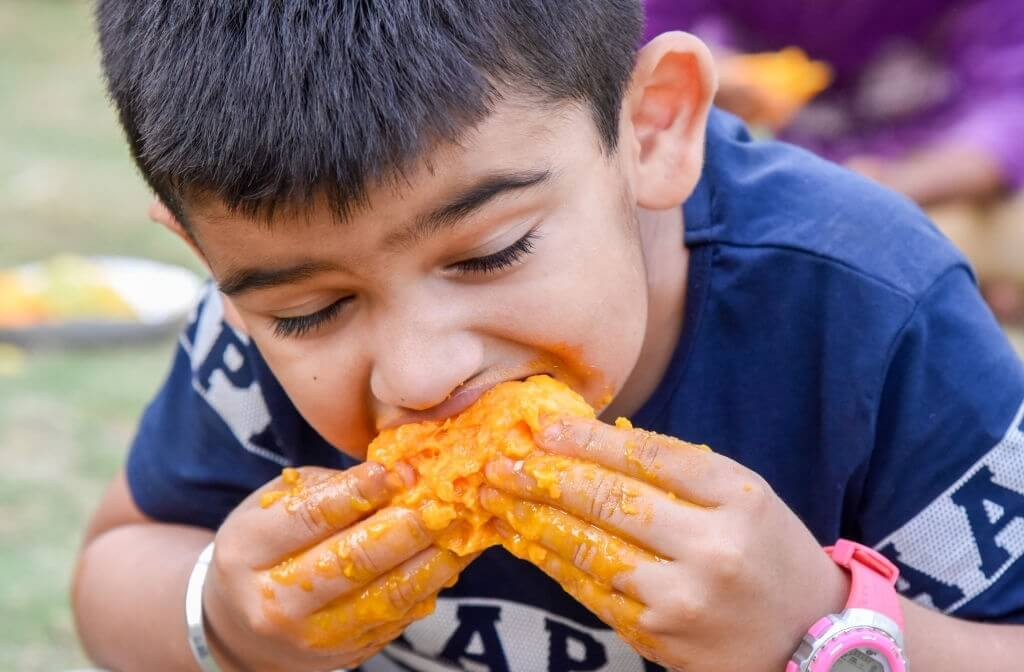 a kid eating mango in competion